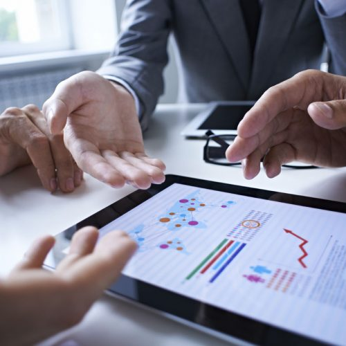 Three business people examining graphs on the screen of digital tablet